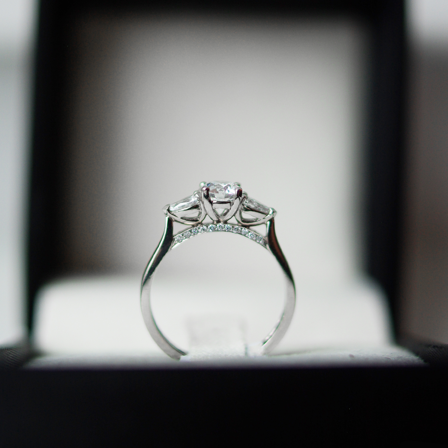 Trilogy Engagement Ring With a Round Brilliant Cut Diamond With Pear Cut Diamond Outers